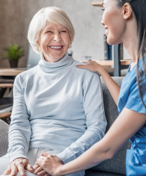 Vertical shot of helpful nurse taking care of senior woman in nursing home