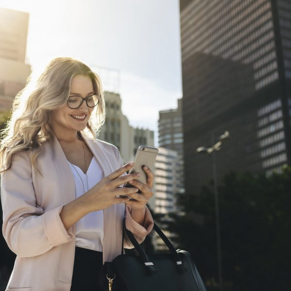 Urban realtor walking in the city using her mobile phone. Businesswoman texting on her smart phone while commuting to work.